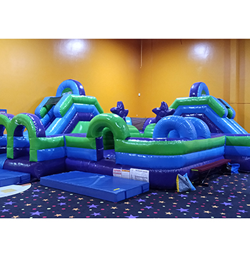 Blue and green obstacle course inflatable with two slides.