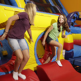 Two kids jumping on a bounce house