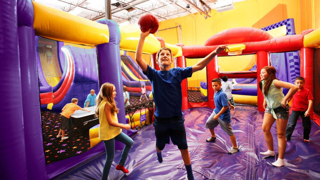 Boy and friends playing basketball on inflatable attraction at BounceU private birthday party