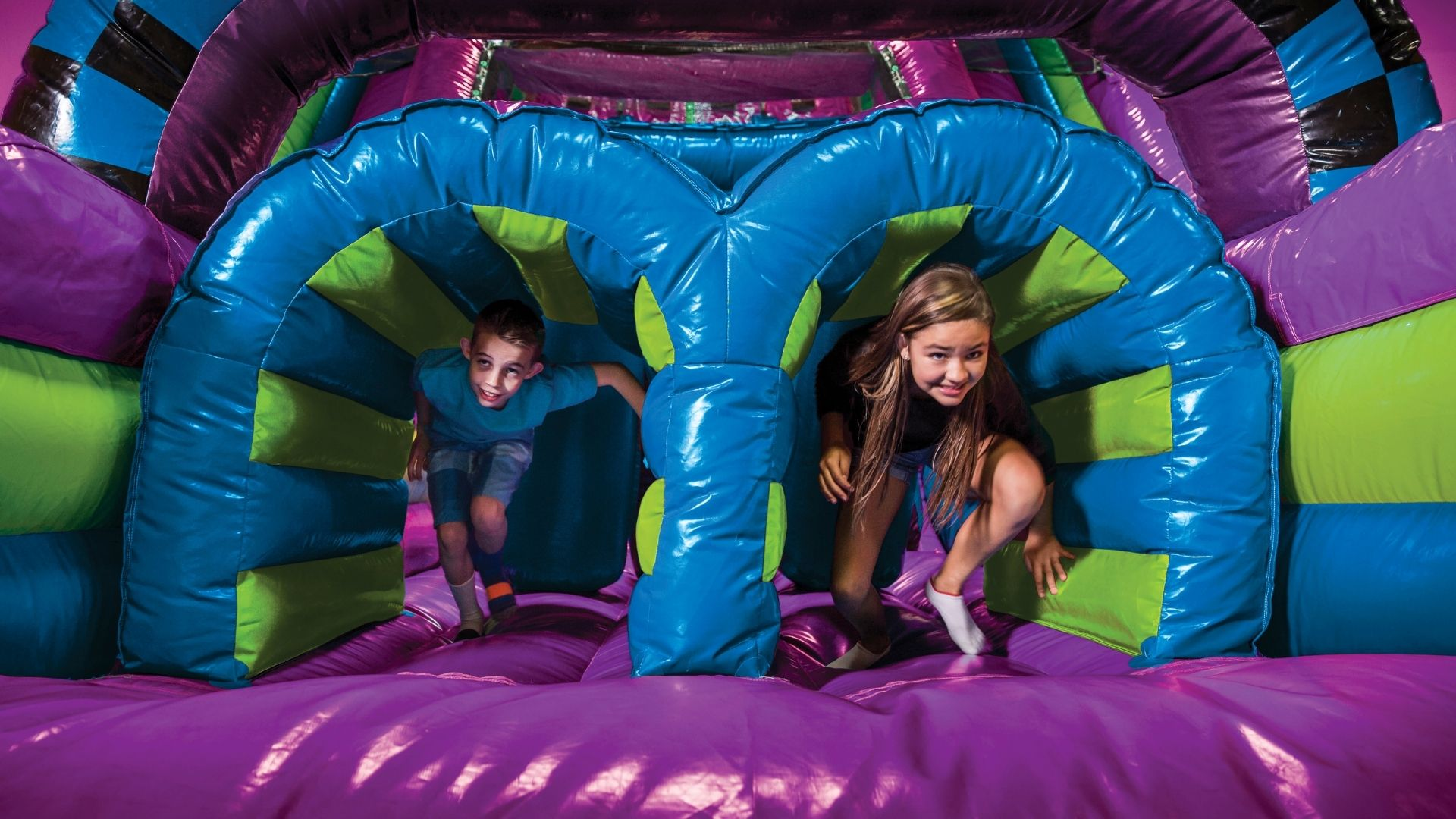 Two kids have fun in a bounce house at a kids birthday party.