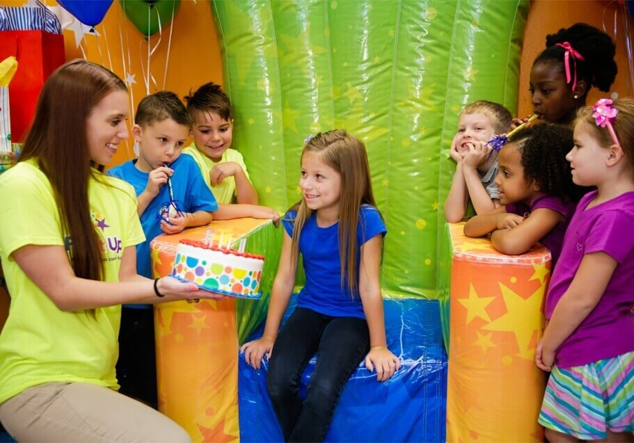 One of our party pros presents a cake to a young girl celebrating her birthday party on one of our inflatable thrones
