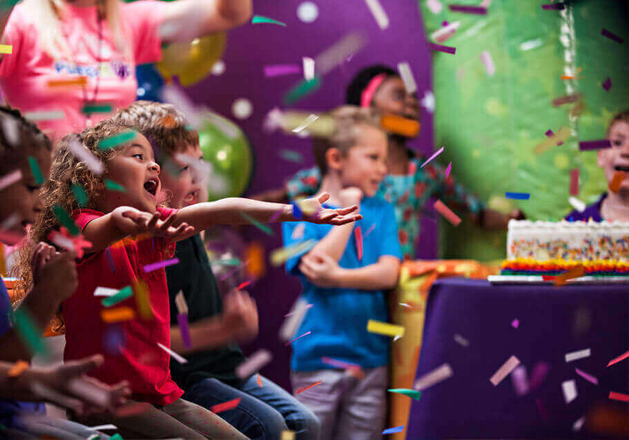 Happy kids celebrating a birthday party with confetti and cake