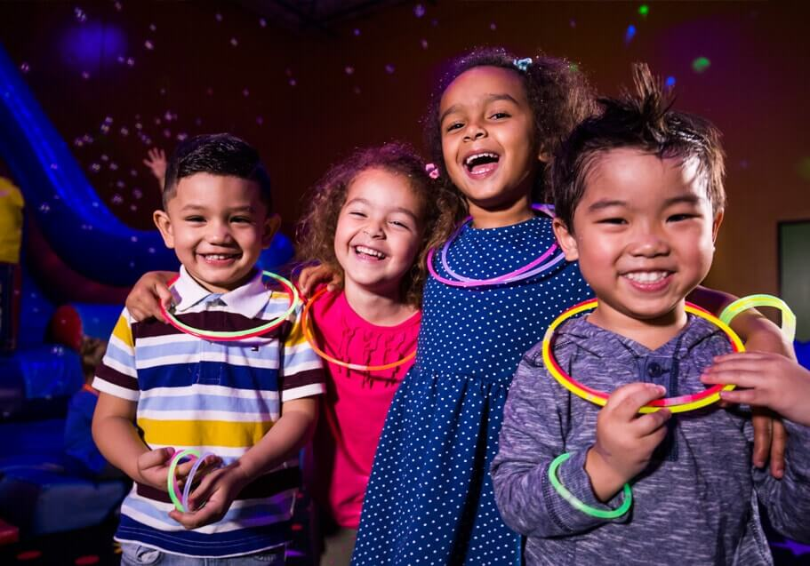 Four kids celebrating birthday with glow experience.