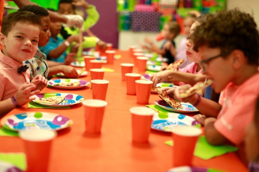 fast food themed party at pump it up with kids sitting at table eating pizza