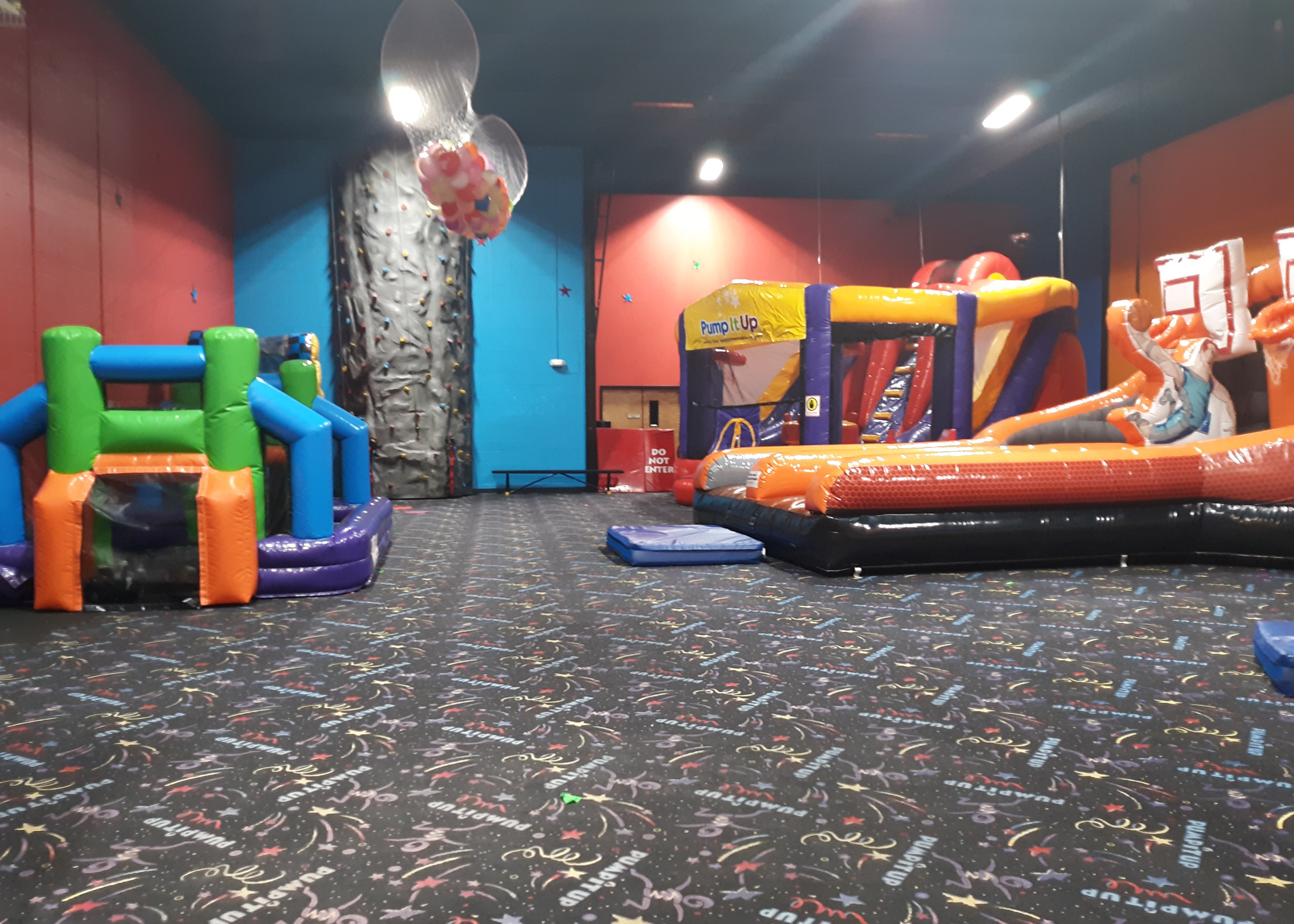 Pump It Up birthday party arena space with large inflatables, toddler area and rock climbing wall.