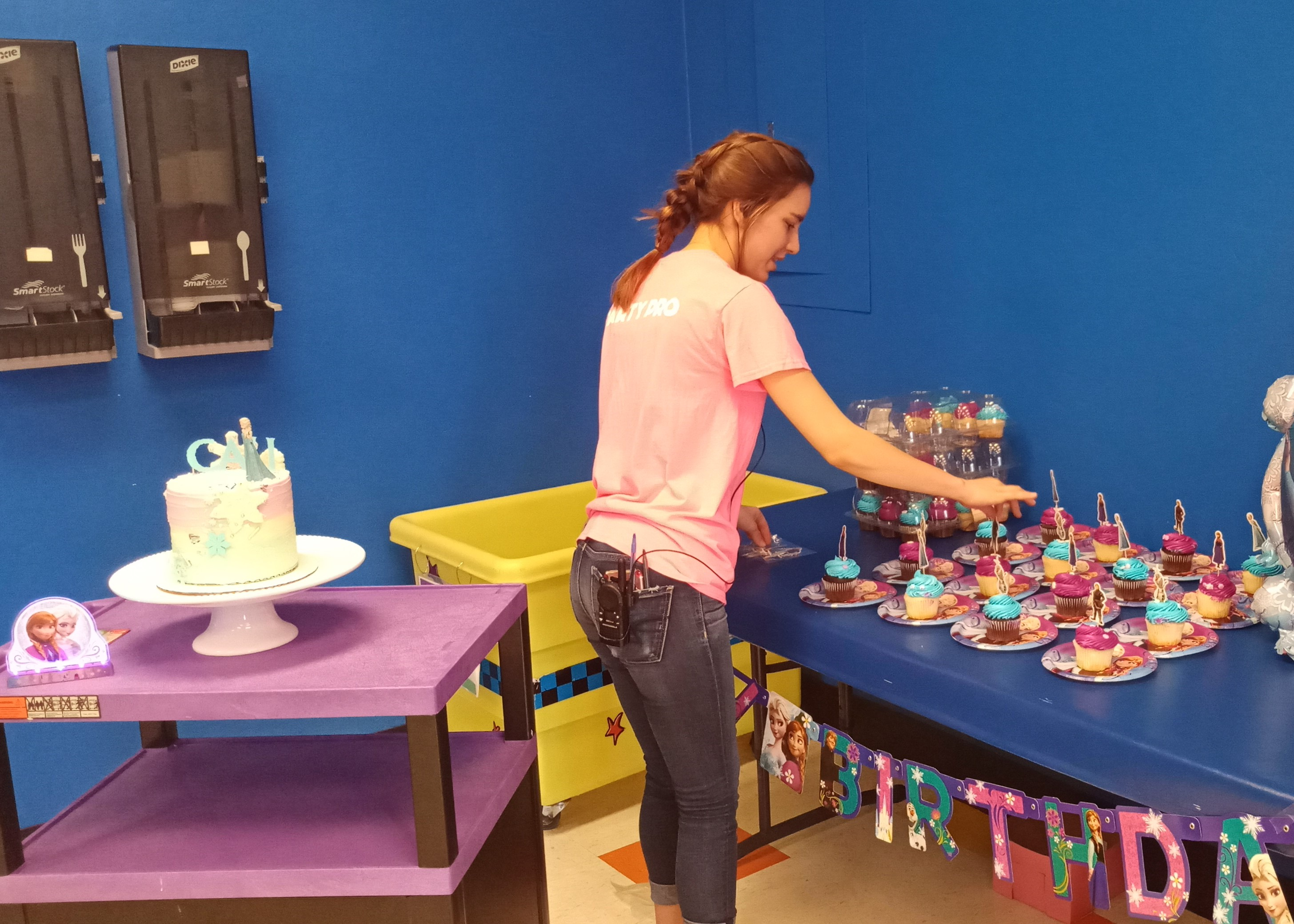 Pump It Up staff setting up cupcakes in the private birthday party room.