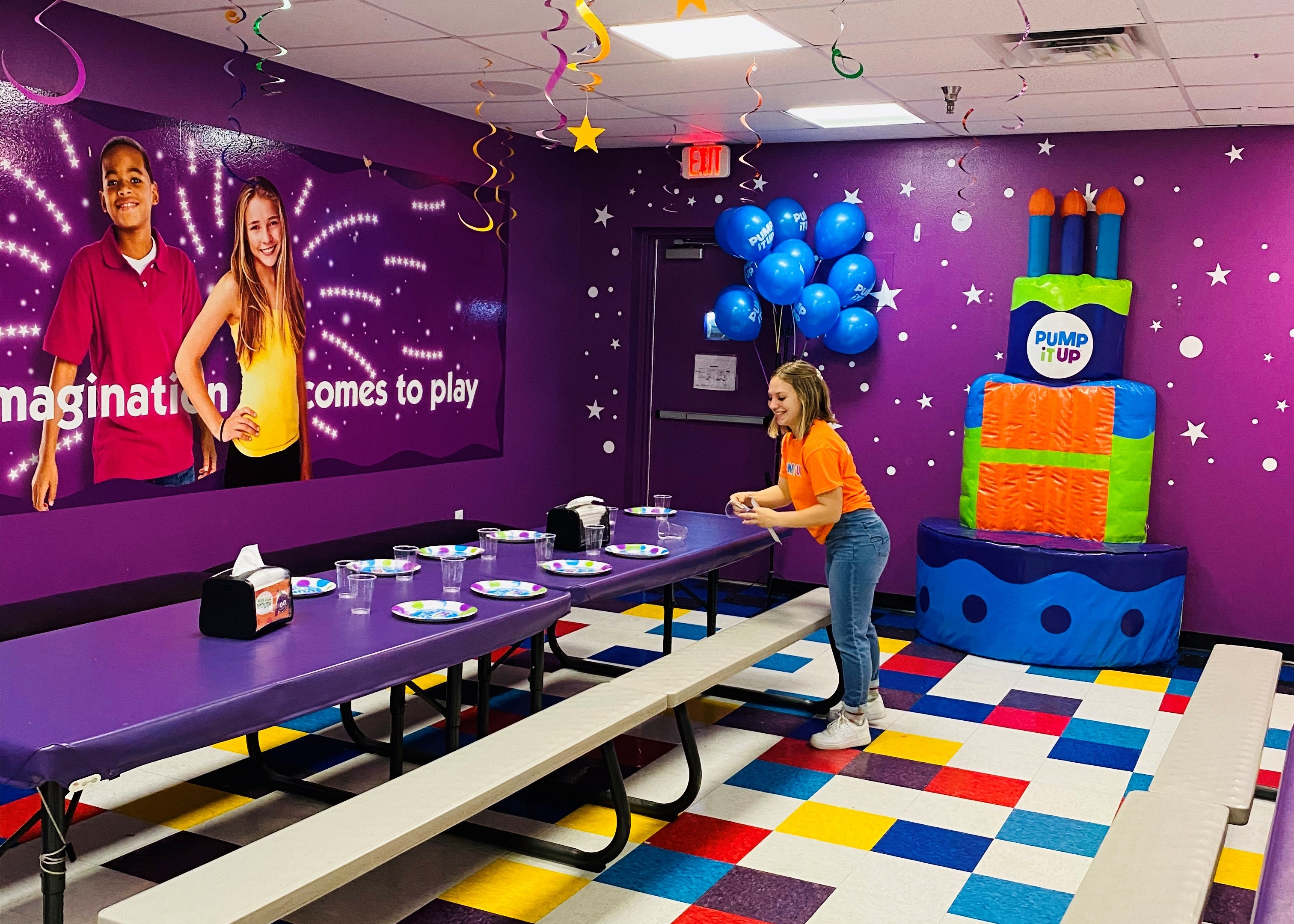 Pump It Up birthday party staff setting up table in private party room and throne for birthday.