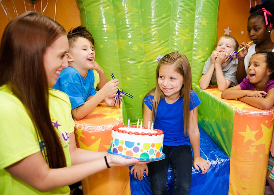 Pump It Up birthday party celebration with birthday child, team member and other kids in the birthday party room.