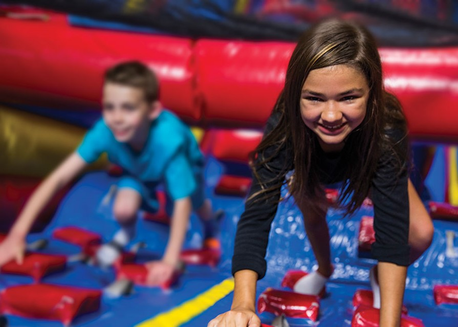 Pump It Up arena space for private parties with kids climbing a large inflatable attraction.