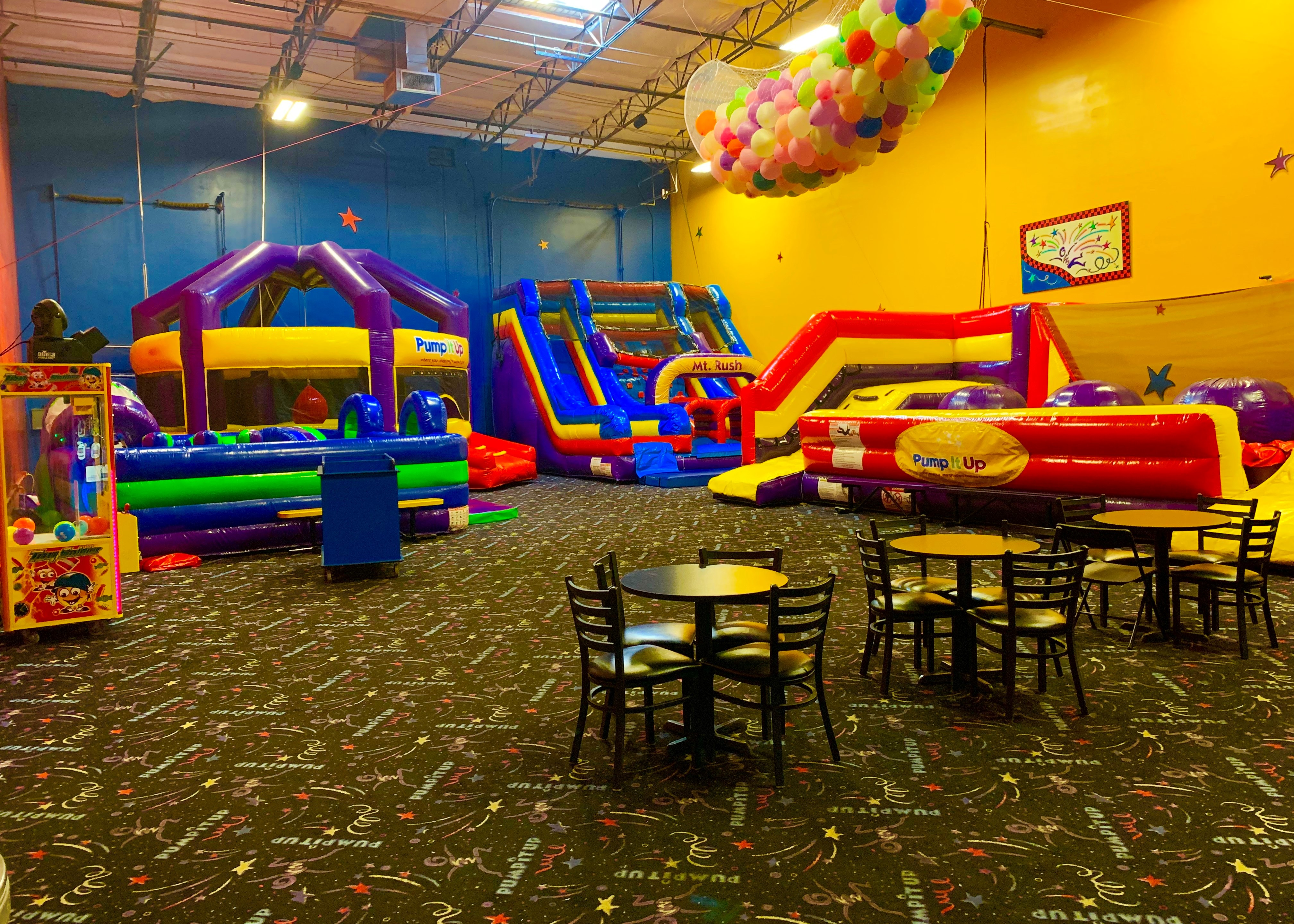 Pump It Up birthday party arena space with three large inflatable rides and tables with chairs for private parties.