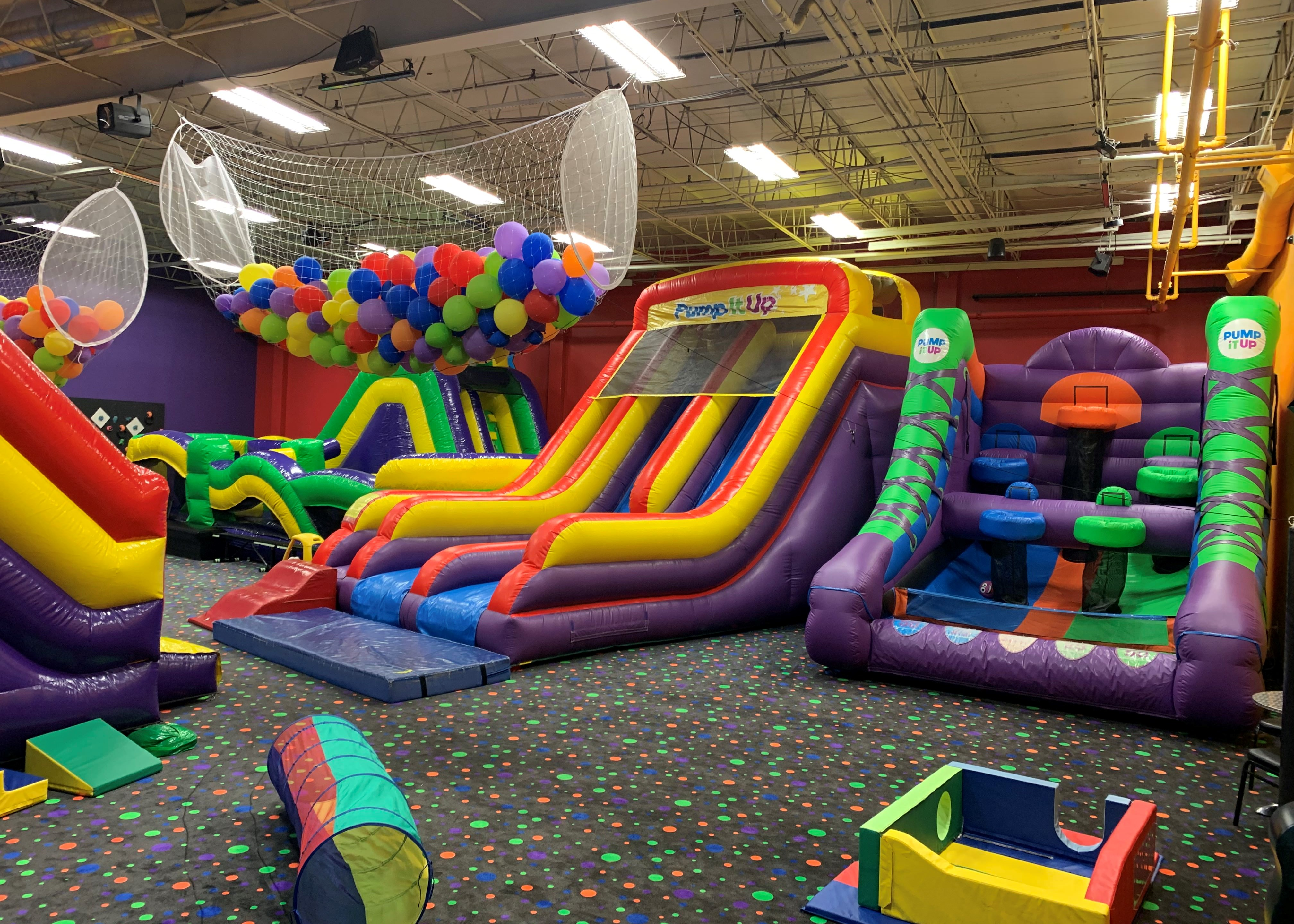 Pump It Up birthday party arena space with four large inflatable rides for private parties.