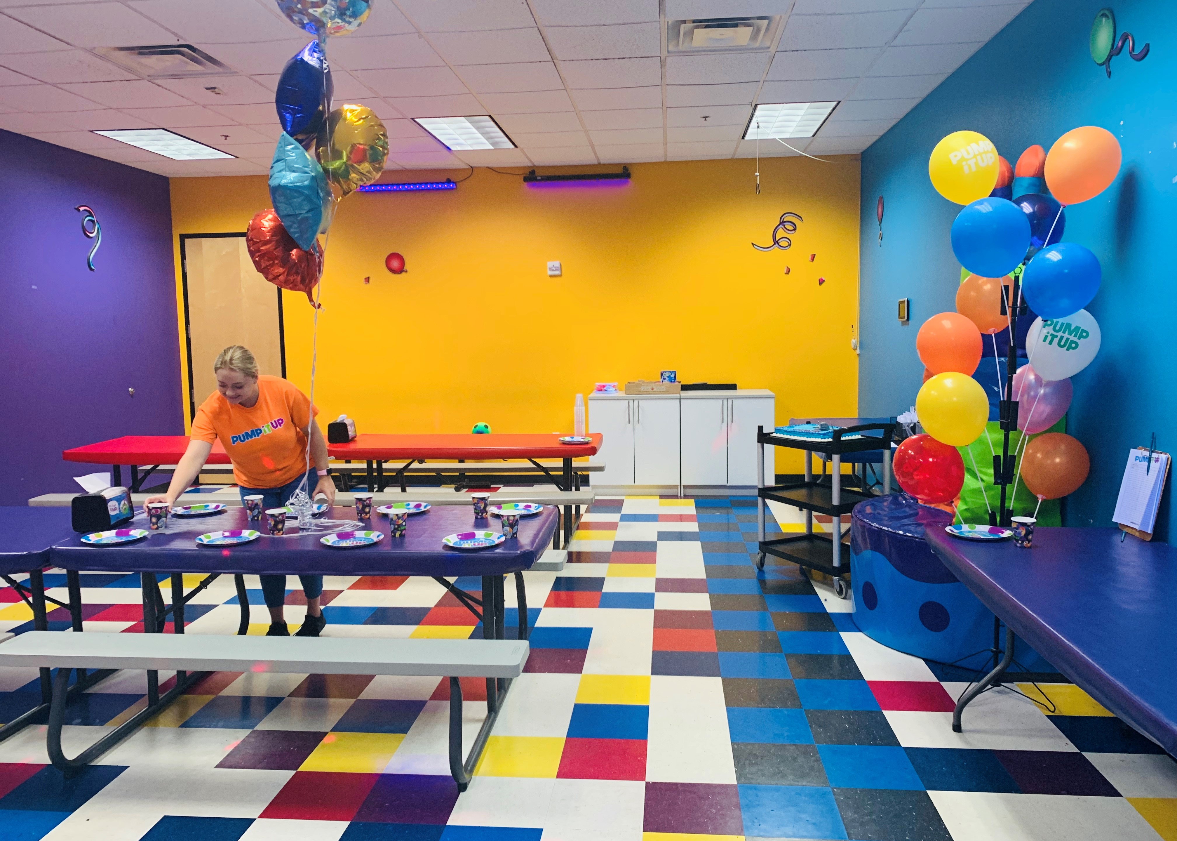 Pump It Up party room with staff setting up table for private party.