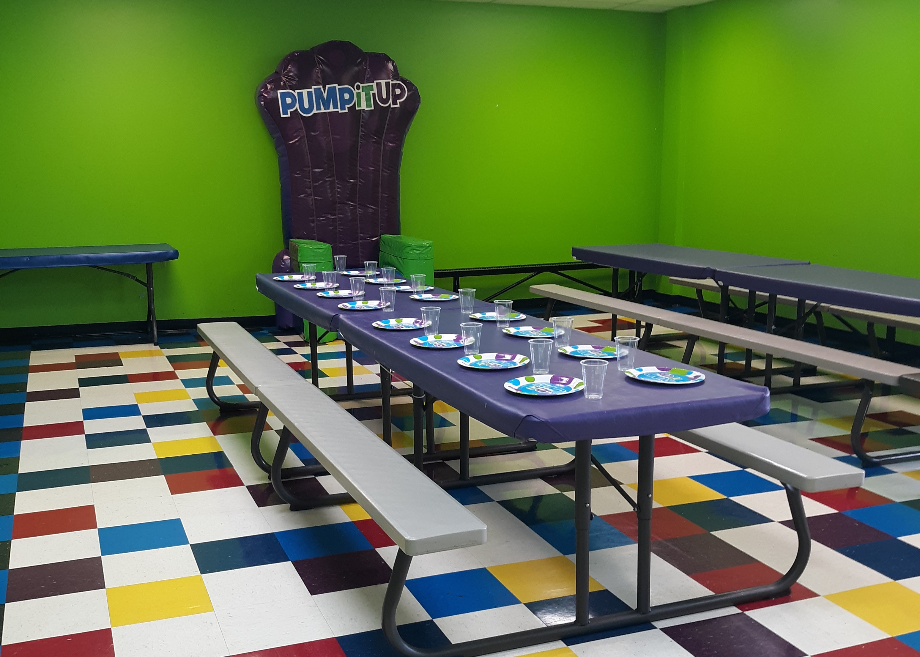 Pump It Up  private birthday party space with tables and inflatable chair for birthday child.