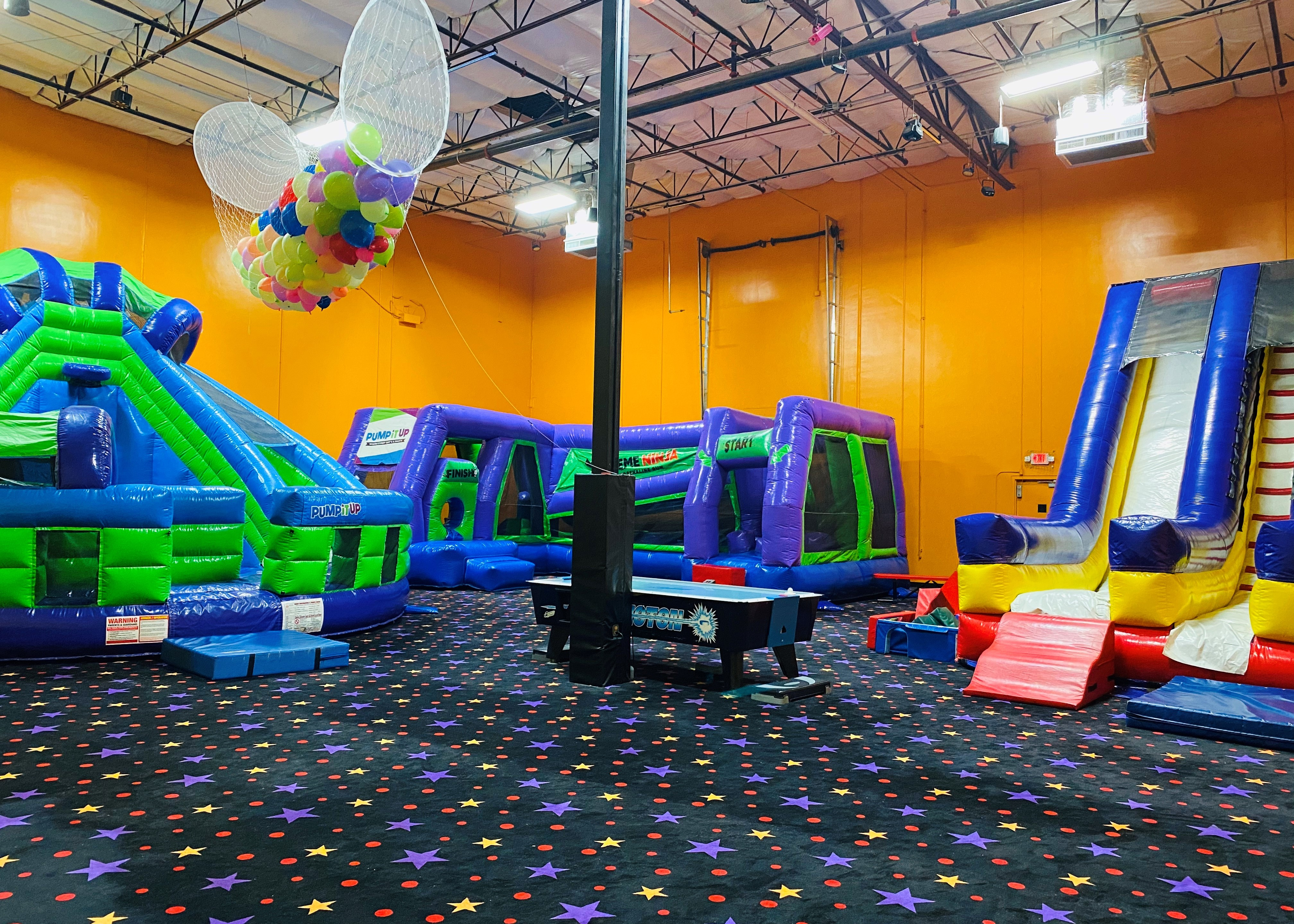 Pump It Up private party arena space with three large inflatables for kids to play.