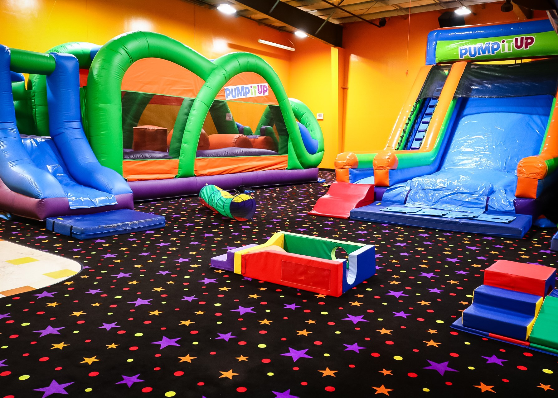 Pump It Up private party arena space with large inflatable rides with toddler soft play toys on the carpet.