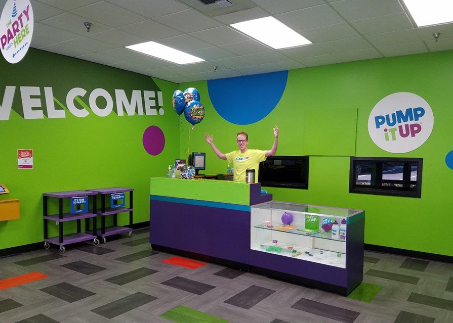 Pump It Up lobby and staff member at the front desk of a kid's birthday party place.