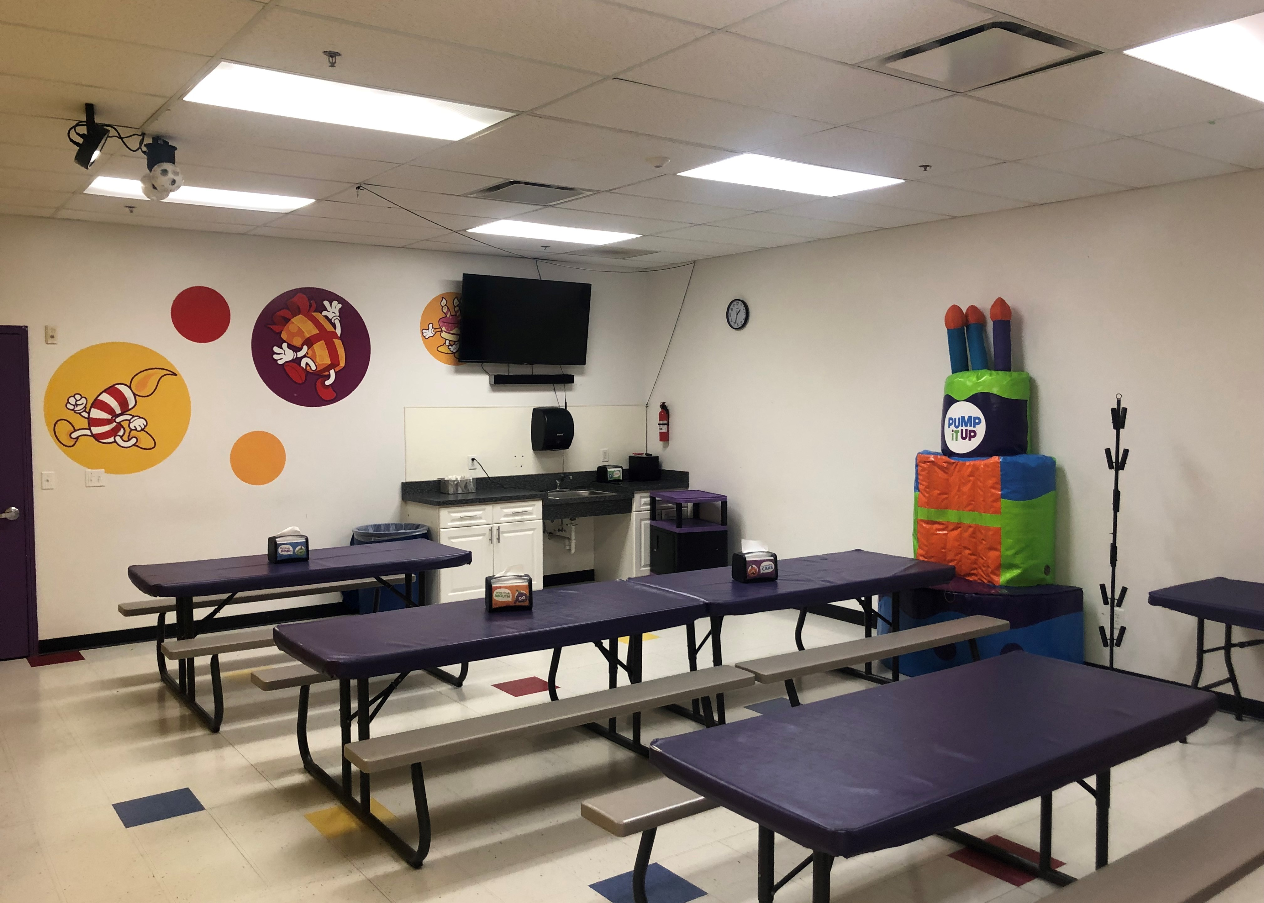 Pump It Up birthday party room with throne for birthday child and tables for guests of the private party.