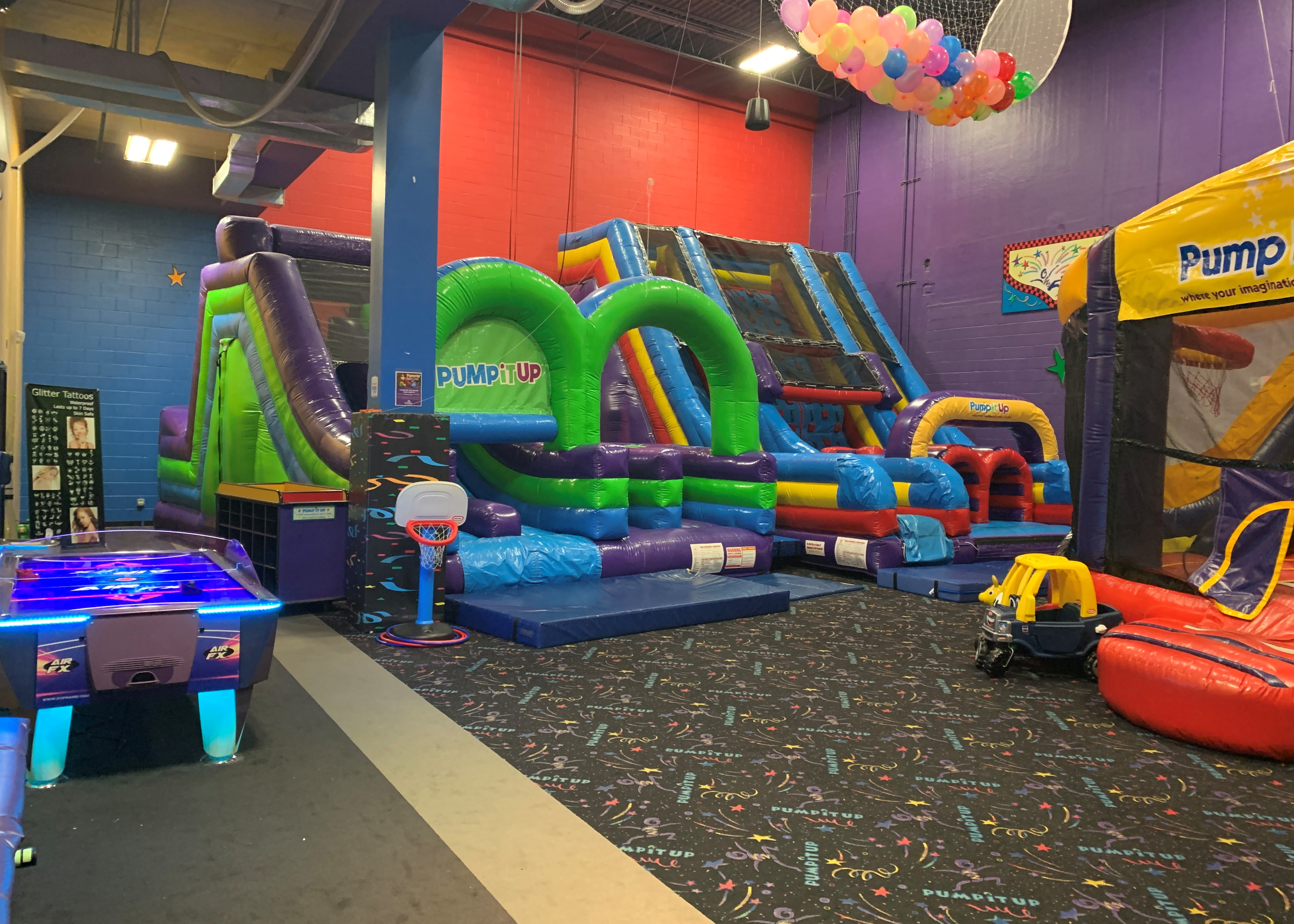 Pump It Up birthday party arena space with three large inflatable rides for private parties.