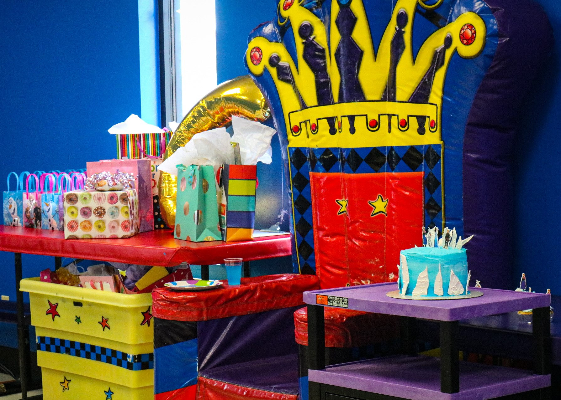Pump It Up birthday party room with throne for birthday child, a cake and presents on a table.