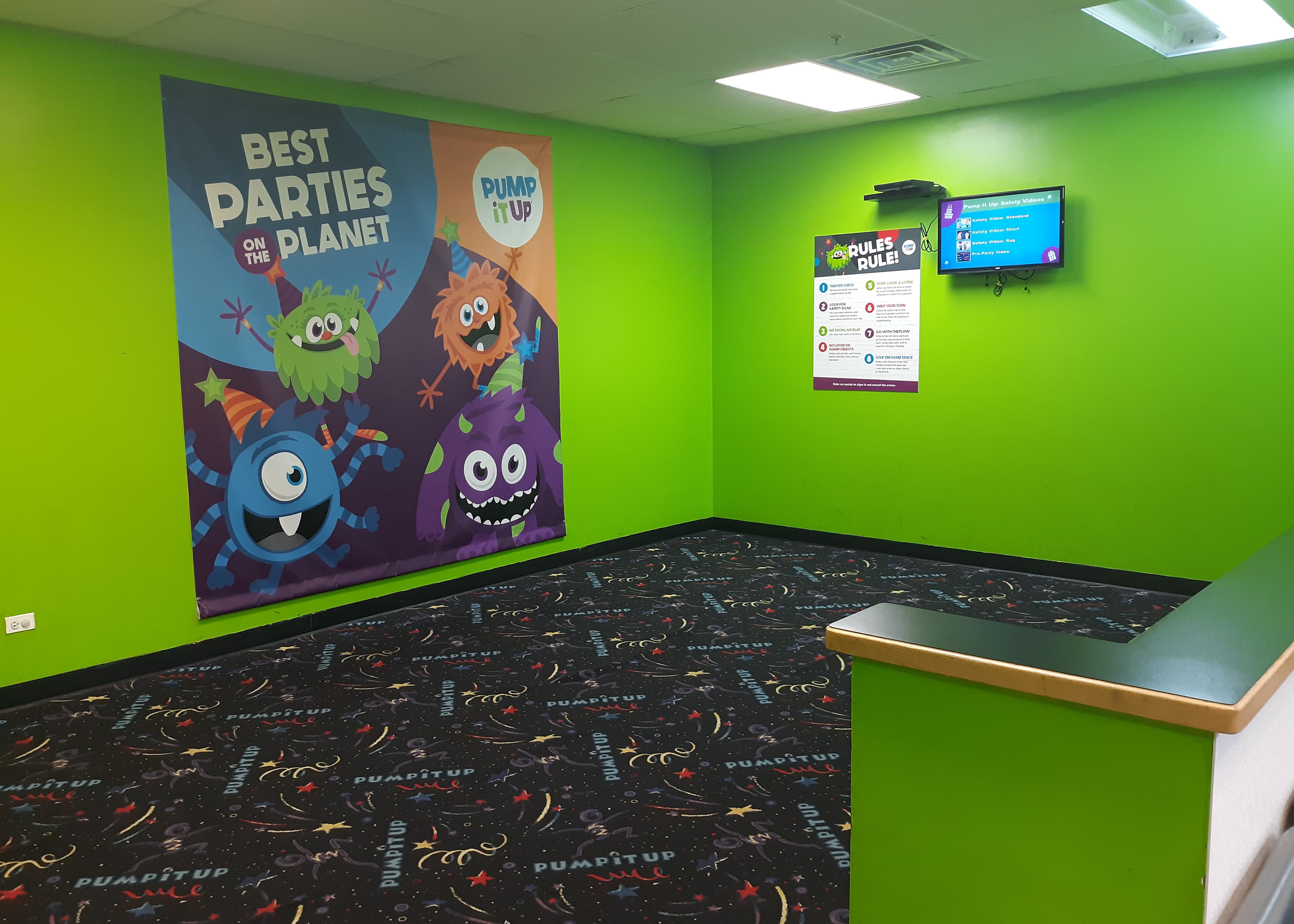 Pump It Up space for party guests with backdrop and tv for safety video.