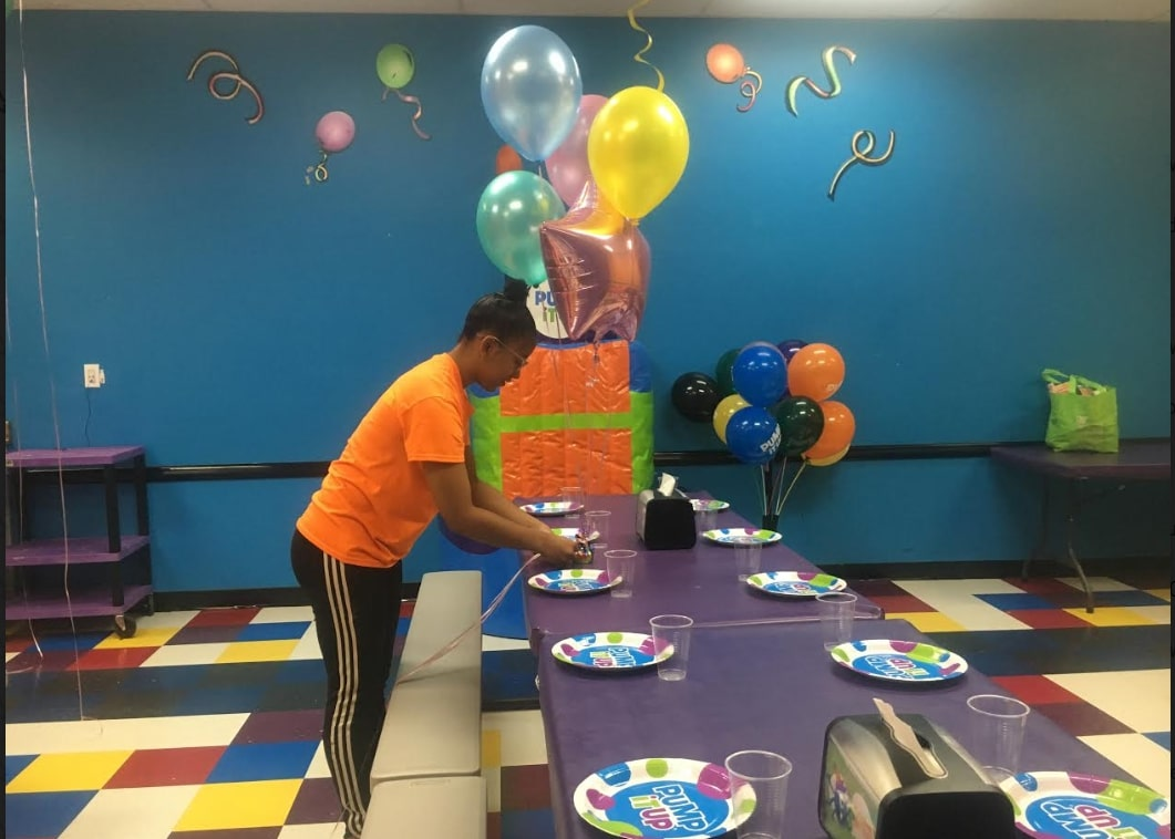 Pump It Up birthday party staff setting up table in private party room.
